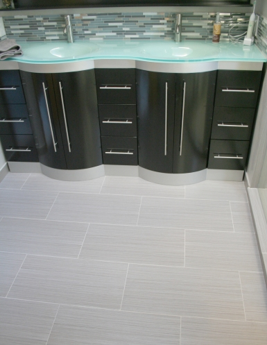 The new large vanity provides a cool modern vibe, while still offering lots of storage. New tile flooring installed over a radiant heat flooring system gives a modern and warm feel to the bathroom.