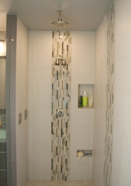 The large reconfigured shower has new tile to the ceiling, two body sprays, a rain shower head in the ceiling and a dual shower head for a spa shower feel. Build in wall storage makes the shower functional as well.